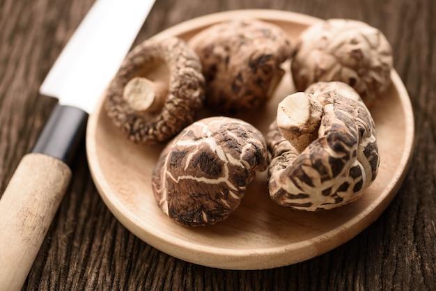 Fungo di shiitake secco in piatto di legno per il fondo dell'alimento
