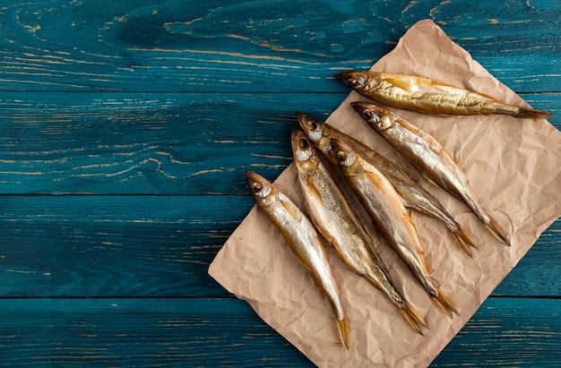 Il pesce essiccato all'odore è uno spuntino ideale per la birra. si trova su una vecchia carta kraft su uno sfondo di tavole di legno blu scuro.