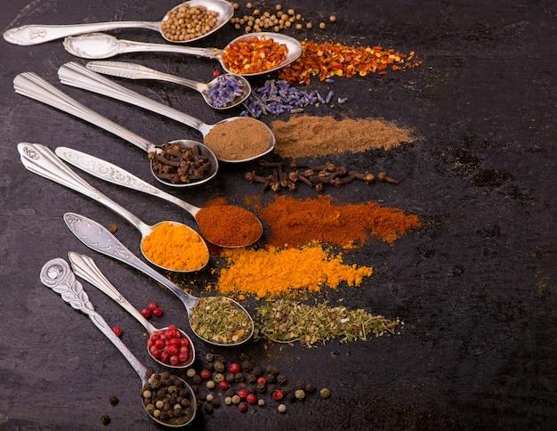 Spezie secche - pepe, curcuma, paprika, anice, lavanda, adjika, coriandolo in cucchiai vecchi su sfondo nero