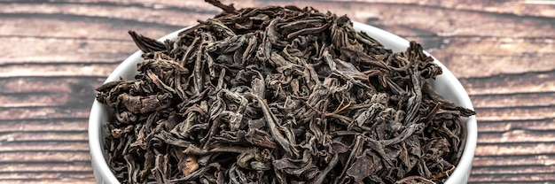 Il tè essiccato viene versato in una tazza di ceramica su un tavolo di legno.