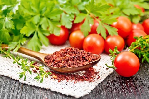 Fiocchi di pomodoro essiccato in un cucchiaio su un tovagliolo di tela, pomodorini freschi, prezzemolo e timo sulla tavola di legno sfondo