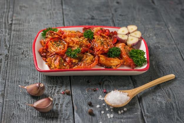 Pomodori secchi con aglio e un cucchiaio di legno con sale marino grande su un tavolo di legno