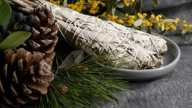 Sbavature di salvia bianca essiccate in stick, relax e aromaterapia. sbavature durante la cerimonia occulta psichica, la guarigione a base di erbe, lo yoga o la pulizia dell'aura. incenso essenziale per rituali esoterici e predizione del futuro.