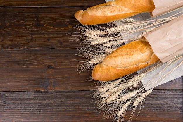 Teste di semi di gambo di grano intero essiccate tra due deliziosi amori di pane francese in sacchetti di carta sul tavolo marrone scuro