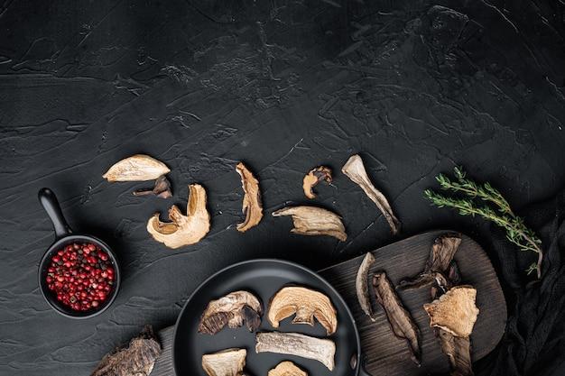 Funghi selvatici secchi impostati in padella in ghisa, su sfondo nero, vista dall'alto laici piatta,