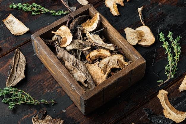 Set di funghi selvatici secchi, sul vecchio fondo di tavolo in legno scuro