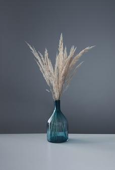 Cereali decorativi gialli secchi in vaso di vetro sulla tavola bianca