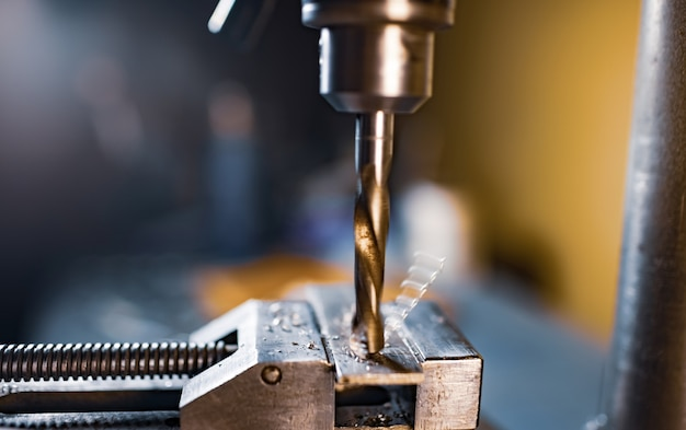 Processo di perforazione con il primo piano dei trucioli sul posto di lavoro in officina