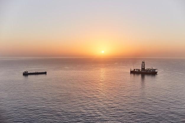 Scaffale dell'oceano del fondo del pozzo di petrolio della perforazione della nave di perforazione gas di esplorazione geologica e giacimenti di petrolio in mare al tramonto
