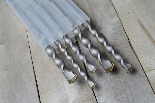 Trapani con punte per martello in metallo duro giacciono in una custodia di plastica su uno sfondo di legno della plancia. avvicinamento.