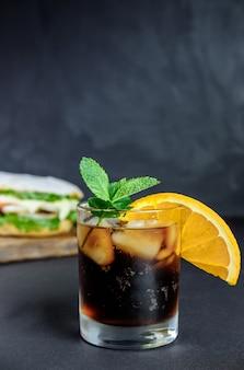 Bere cocktail con panino grande cibo di strada, fast food.