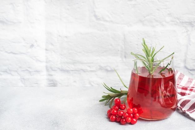 Bere dalle bacche di viburno rosso in tazza di vetro.