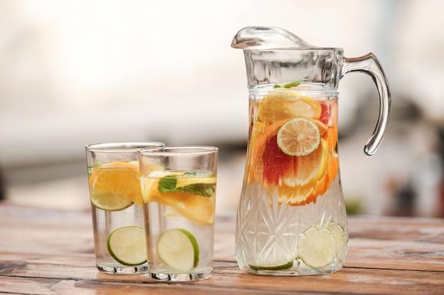 Bevi sano! primo piano del barattolo e due bicchieri con limonata sul tavolo di legno