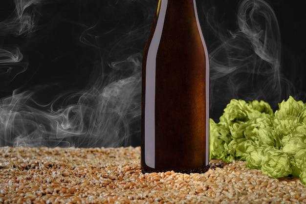 Bere serie di mockup. bottiglia di birra marrone con riflessi che si erge su grano e cono di luppolo su uno sfondo nero per studio con fumo. il modello può essere utilizzato sulla tua vetrina.