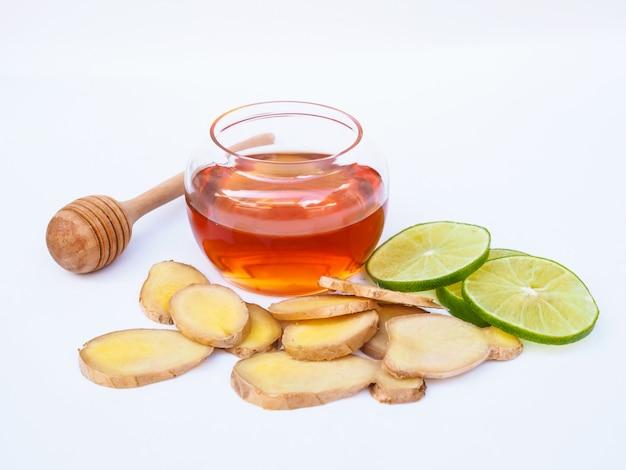 Bere gli ingredienti del tè con zenzero alle erbe e agrumi limone lime e miele isolato su uno spazio bianco.