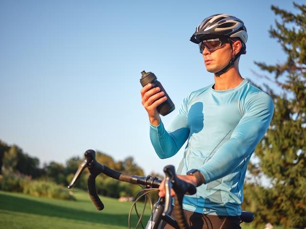 Bevi un ciclista maschio professionista assetato che tiene una bottiglia con acqua in piedi con la sua bici dentro