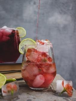Un drink con cubetti di ghiaccio con fiori in un bicchiere