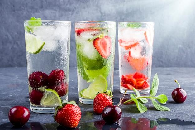 Da bere con fragola, lime, ciliegia e menta su sfondo scuro. cocktail mojito