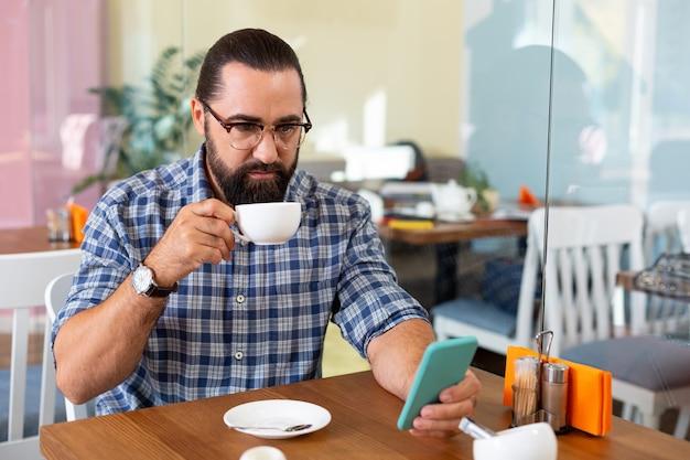 Bevendo caffè. uomo barbuto con gli occhiali leggendo la rivista online sul suo telefono e bevendo caffè