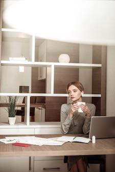 Bevendo caffè. donna di affari che beve un caffè mentre lavora al computer portatile e completando i suoi compiti