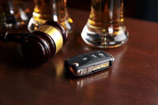 Bere e guidare il concetto. chiave della macchina su un tavolo di legno, sfondo di un pub