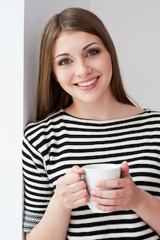 Bere caffè fresco. bella giovane donna in abiti a righe appoggiata al muro e tenendo la tazza