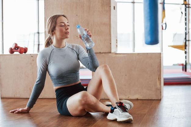 Bere acqua fresca. la giovane donna allegra ha una giornata di fitness in palestra al mattino