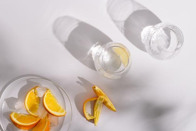 Bere acqua naturale e ghiaccio in bellissimi bicchieri di vetro e fetta di arancia fresca sul piatto.