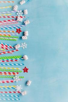 Bere cannucce colorate di carta per cocktail di capodanno sulla superficie azzurra. biglietto natalizio.