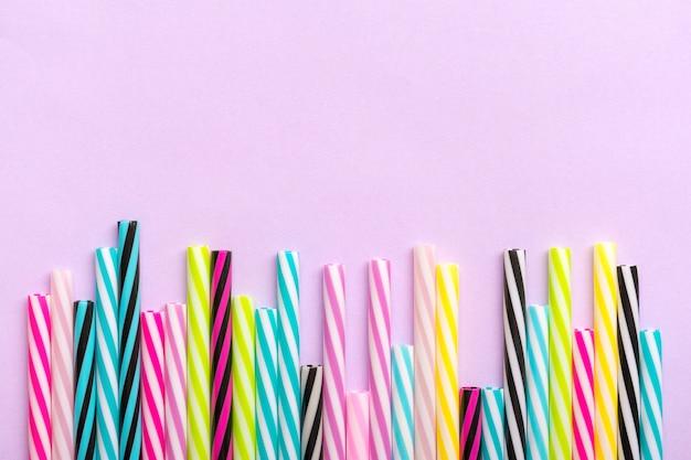 Cannucce con strisce per la festa su sfondo lilla. vista dall'alto di tubi di plastica colorati per cocktail estivi. disteso