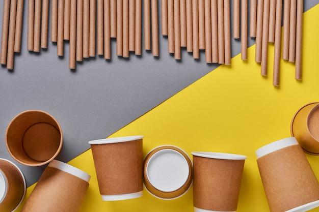 Tubi per bere in carta e amido di mais, materiale biodegradabile e bicchieri di carta ecologica su sfondo giallo di tendenza colore 2021. zero rifiuti e concetto senza plastica. vista dall'alto.