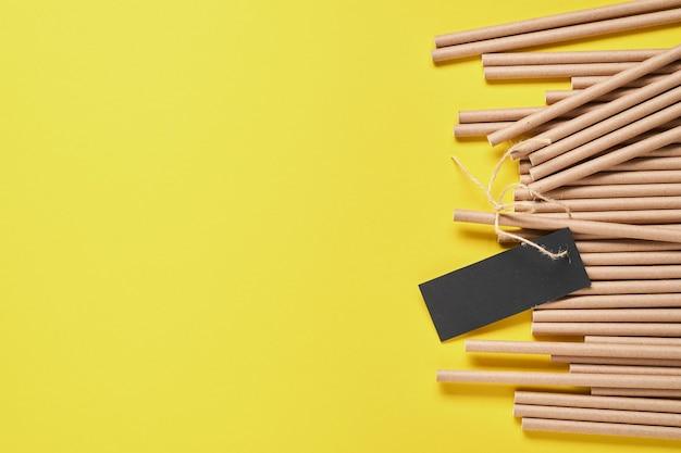 Bere tubi in carta e amido di mais, materiale biodegradabile su uno sfondo giallo