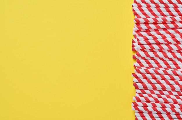 Tubi per bere in carta rossa e marrone e amido di mais, materiale biodegradabile su sfondo giallo di colore di tendenza 2021. concetto di rifiuti zero. vista dall'alto.