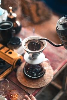 Drip coffee, barista versando acqua sul caffè macinato con filtro, erogazione del caffè