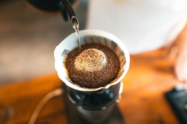 Caffè a goccia, barista che versa acqua sul caffè macinato con filtro, preparazione del caffè