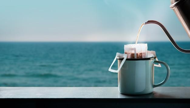 Caffè gocciolante in riva al mare al mattino facendo una bevanda calda con un sacchetto antigoccia per caffè istantaneo