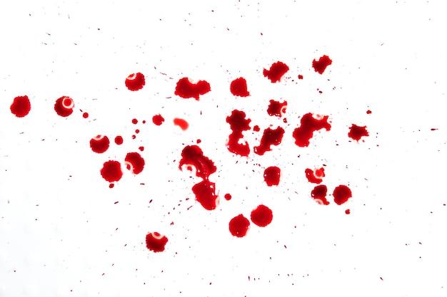 Spruzzata di sangue rosso gocciolante, concetto di orrore e emergenza, isolato su sfondo bianco. molte gocce di sangue rosso sul pavimento bianco.