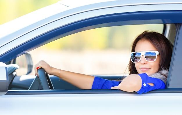 Driver della ragazza di auto in occhiali da sole