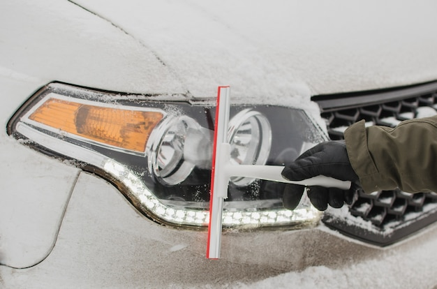Un autista che pulisce i fari di un'auto dalla neve in inverno.