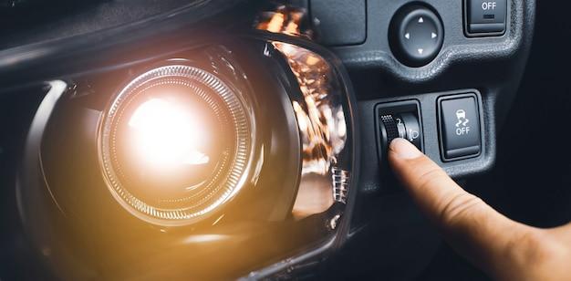 Interruttore di livello dei fari con regolazione manuale della mano del conducente e fari luminosi dell'auto