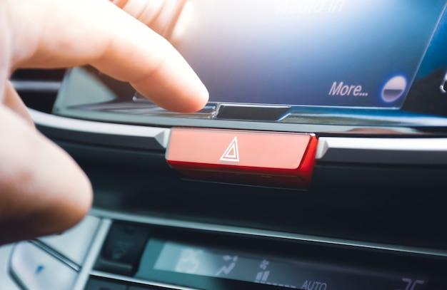 Mano del conducente premendo l'interruttore del pulsante delle luci di emergenza sul cruscotto dell'auto