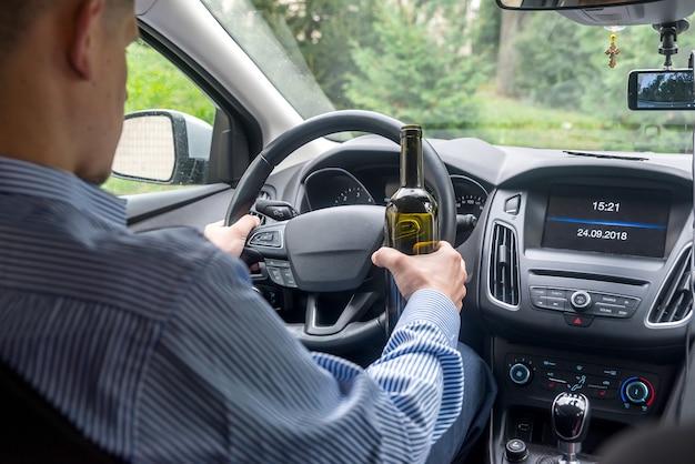 Autista che tiene il volante e una bottiglia di bevanda alcolica