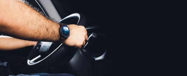 L'autista guida l'auto di notte e lo sfondo nero con spazio per le copie
