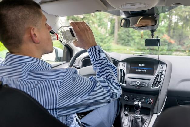 Uomo del conducente che beve alcol durante la guida dell'auto