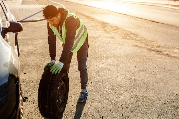 L'autista dovrebbe sostituire la vecchia ruota con una di scorta. uomo che cambia ruota dopo un guasto alla macchina. trasporto, concetto di viaggio. il lavoratore cambia una ruota rotta di un'auto.