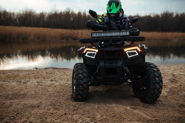 L'autista si siede su un quad sullo sfondo il fiume e la sabbia. sport e concetto estremo