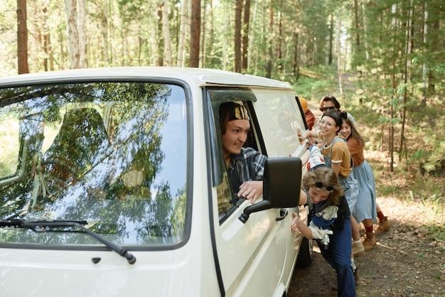 Autista seduto in un furgone rotto con persone che lo spingono insieme sullo sfondo nella foresta