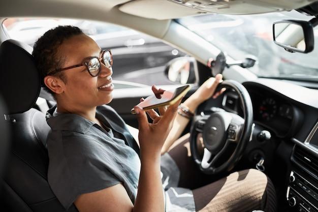 Autista seduto in macchina e parlando al cellulare durante la guida