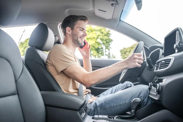 Autista. sorridente giovane adulto in maglietta e jeans alla guida di un'auto che parla sullo smartphone durante il giorno