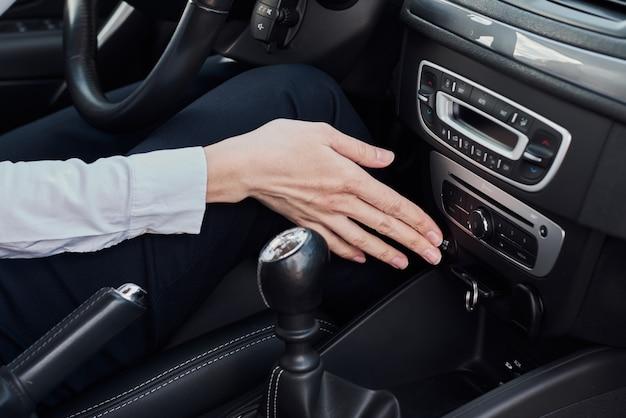 Driver che avvia il motore dell'automobile con il sistema keyless. pulsante di avvio stampa donna